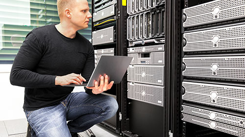 Engineer checking over servers in a data centre